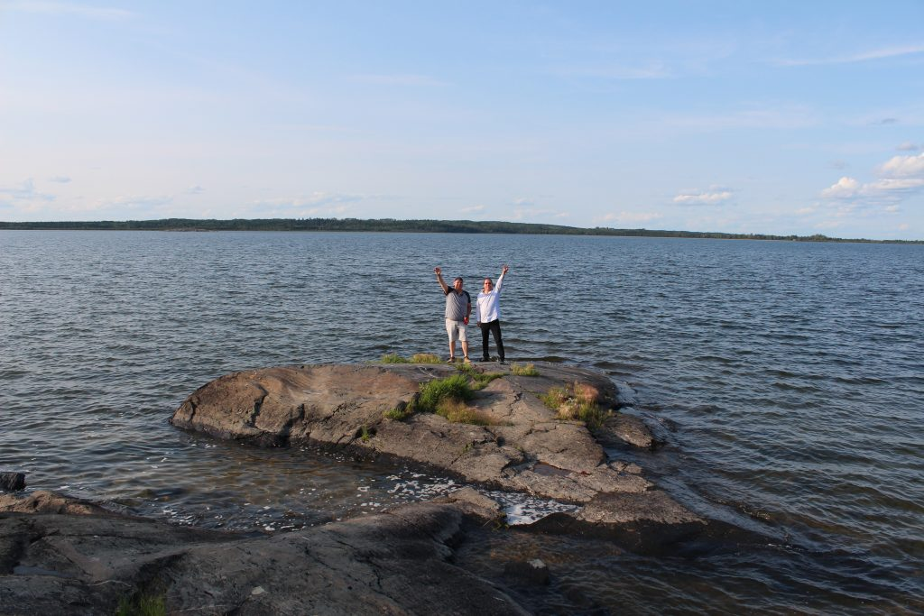 Grand Chief Settee stands on a rock in a body of water along with Bunibonibee Councillor Luke Muskego