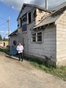 Grand Chief Settee stands in front of one of the original houses of Bunibonibee