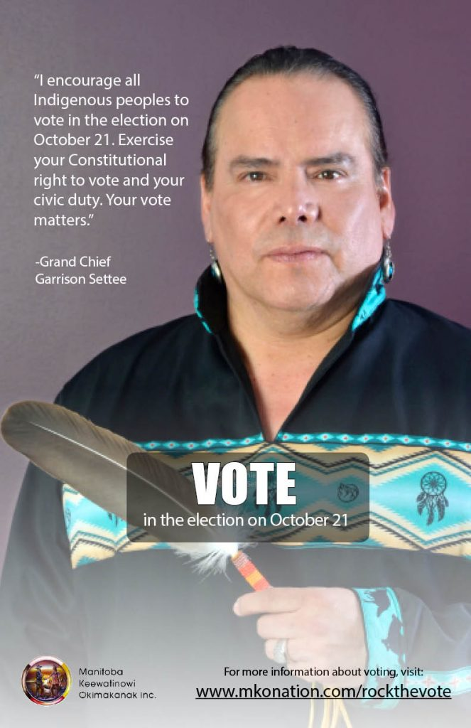 A picture of Grand Chief Settee holding an eagle feather