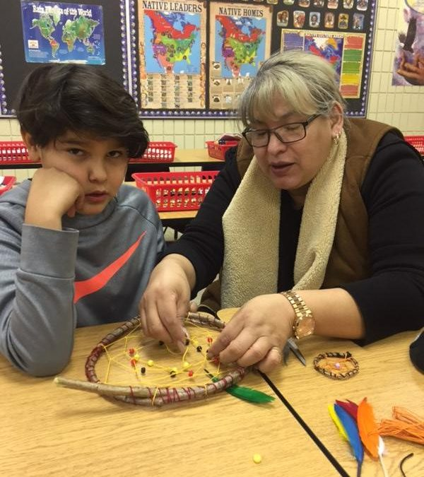 A young boy and his mother make a dreamcatcher