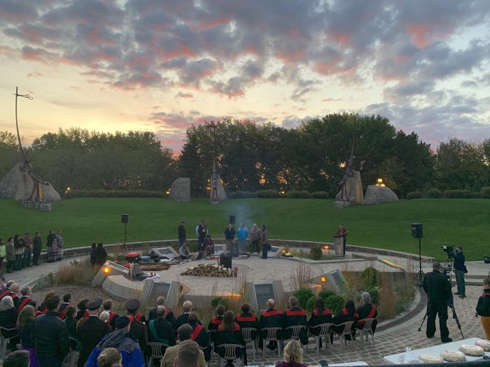 A group of people gathered in the Oodena Circle at The Forks