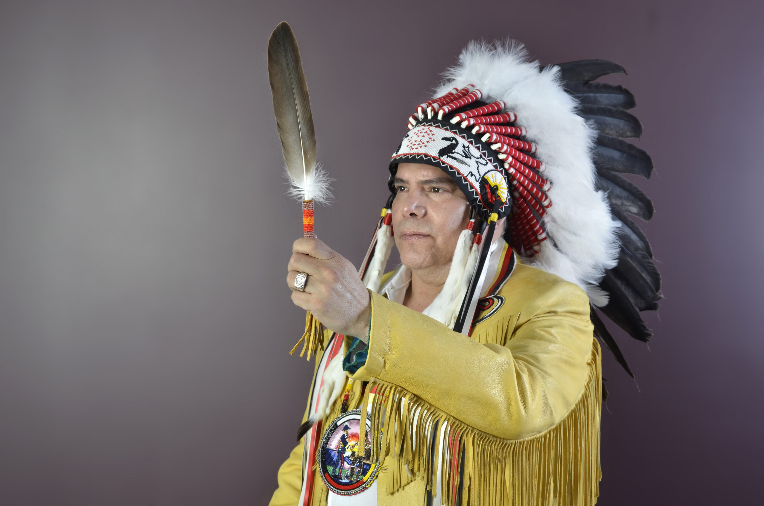 Grand Chief Settee holding an eagle feather