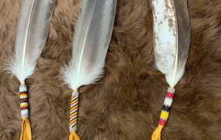 Three eagle feathers sitting on top of buffalo fur