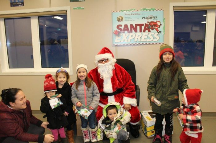 A group of children look happy with Santa Claus