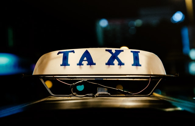"""A sign that says """"Taxi"""" on it"""