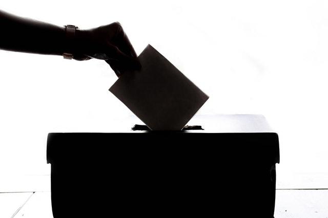 hand putting a ballot into a ballot box